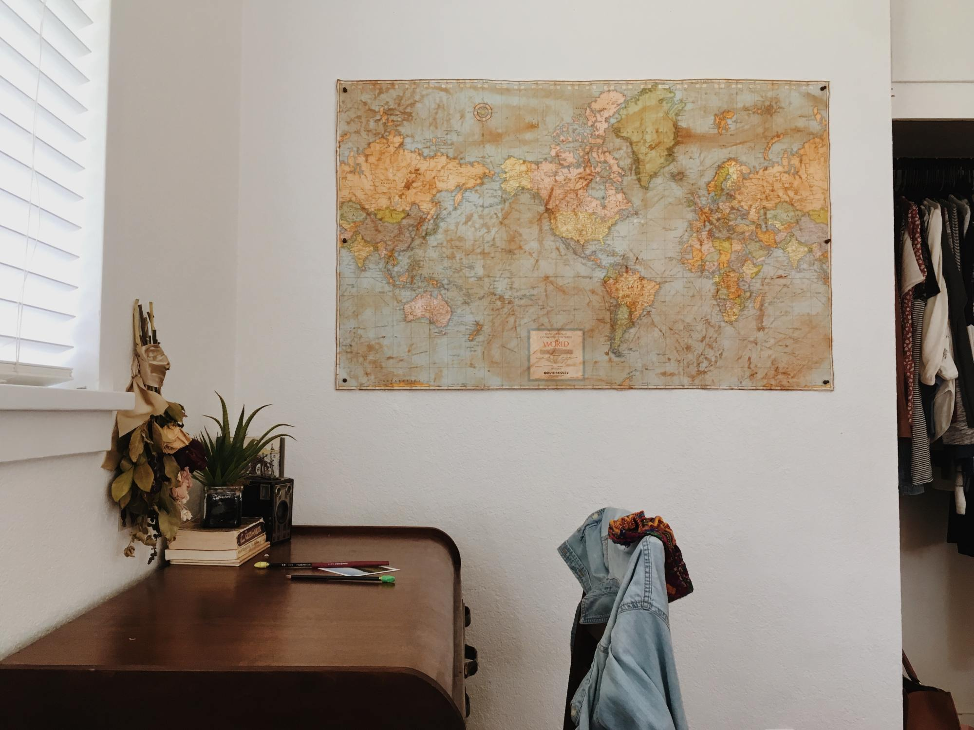 Wooden desk against a wall that has a world map hanging